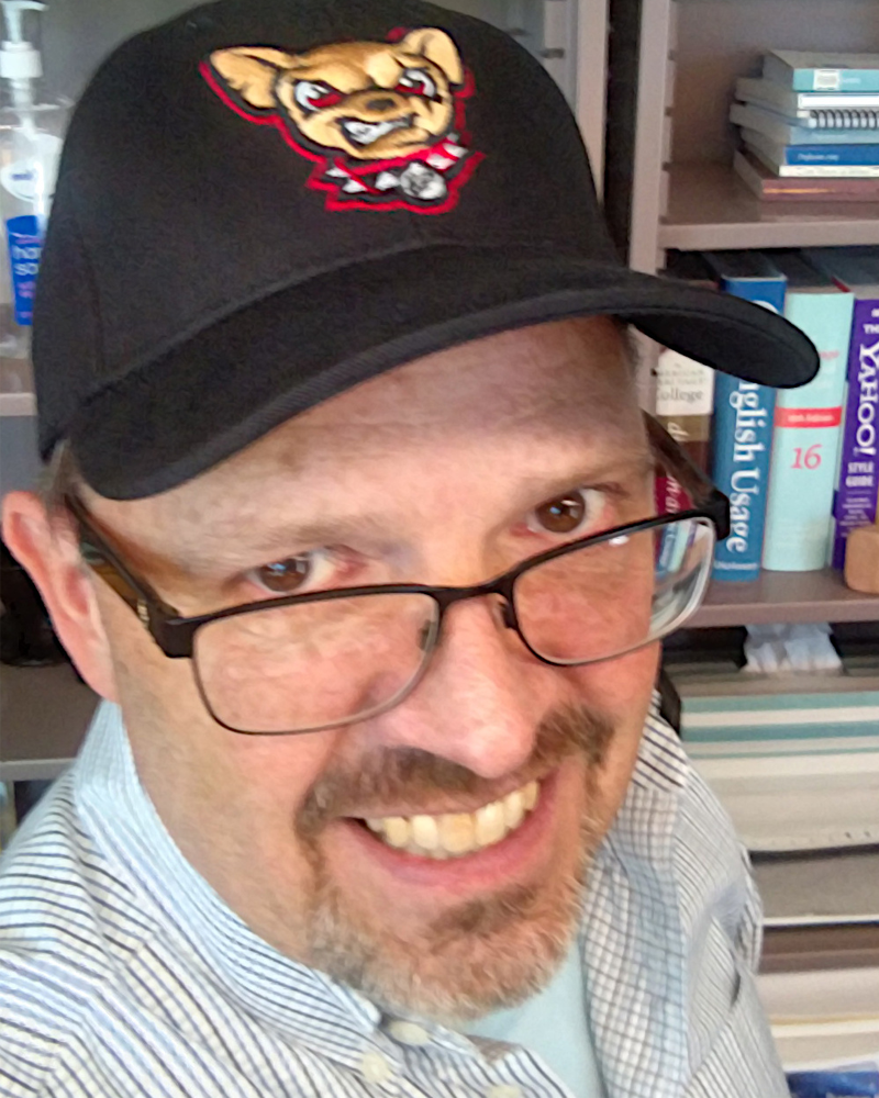 headshot of a man with a black cap wearing a striped button-up and large, rectangular glasses