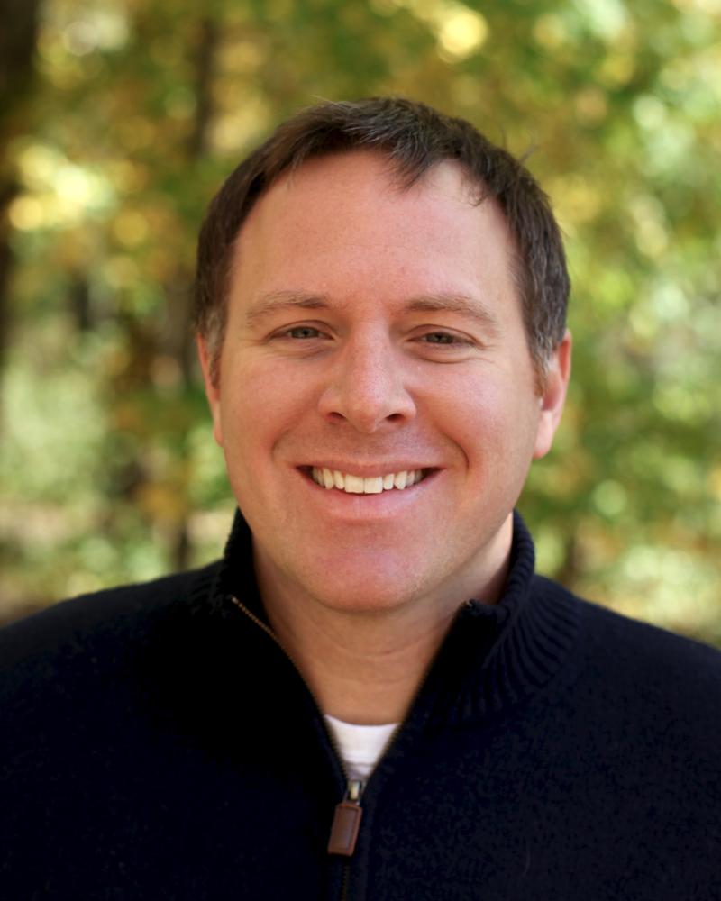 headshot of a man with short, dark hair wearing a quarter-zip